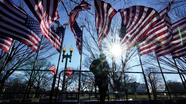 Рабочий устанавливает американские флаги в Вашингтоне