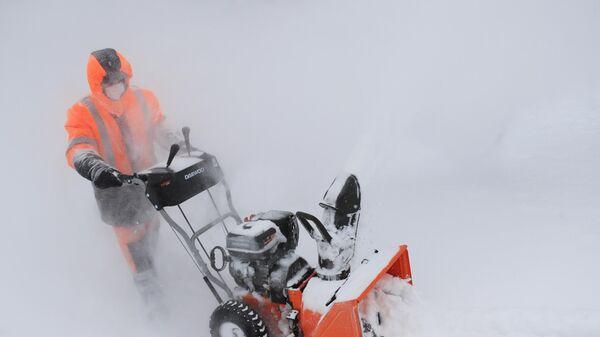 Сотрудник коммунальной службы убирает снег в Москве