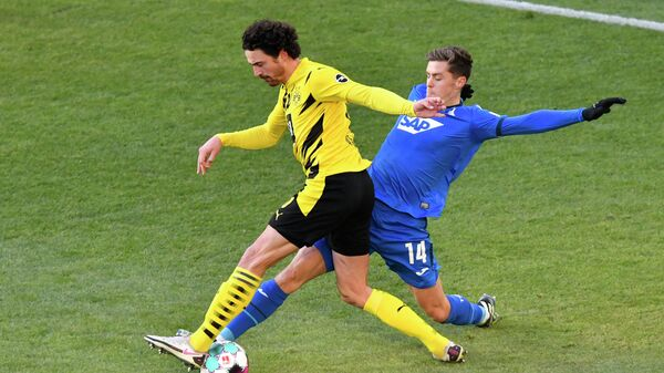 Hoffenheim's Austrian midfielder Christoph Baumgartner (R) and Dortmund's Danish midfielder Thomas Delaney vie for the ball during the German first division Bundesliga football match between Borussia Dortmund and TSG 1899 Hoffenheim in Dortmund, western Germany, on February 13, 2021. (Photo by Martin Meissner / POOL / AFP) / DFL REGULATIONS PROHIBIT ANY USE OF PHOTOGRAPHS AS IMAGE SEQUENCES AND/OR QUASI-VIDEO