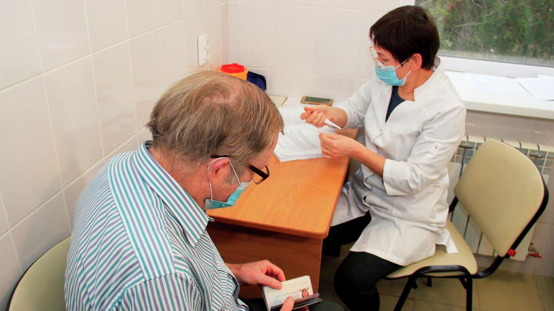 Гражданин США Брюс Уотс Бевен оформляет документы для вакцинации от коронавируса российской вакциной Спутник V (Гам-КОВИД-Вак) в поликлинике в Евпатории - РИА Новости, 1920, 13.03.2021