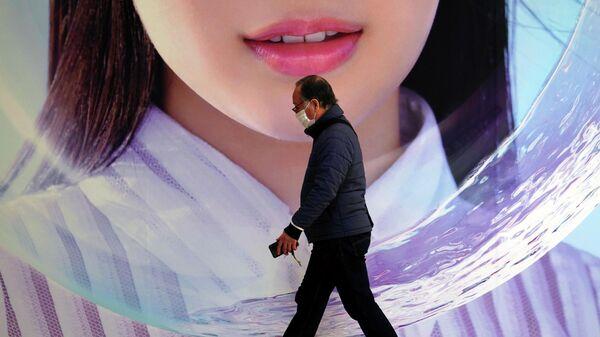 Мужчина в защитной маске проходит мимо рекламного щита в Токио
