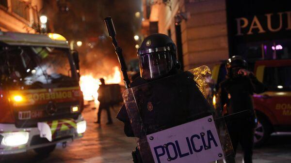 Сотрудник полиции во время акции протеста в поддержку рэпера Пабло Аселя, приговоренного к девяти месяцам заключения за оскорбление монархии и прославление леворадикального терроризма, на площади Пуэрта-дель-Соль в Мадриде