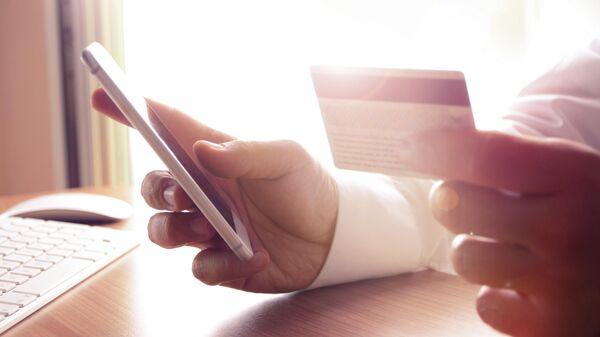 Мужчина с банковской картой и смартфоном