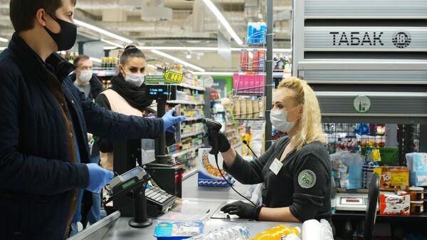 Покупатель оплачивает покупки на кассе в супермаркете