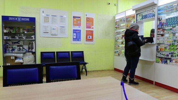 Покупатель у первого аптечного пункта, открытого при московском отделении Почты России