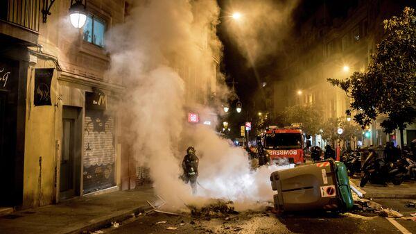 Пожарные тушат огонь во время акции протеста в связи с задержанием рэпера Пабло Аселя в Барселоне