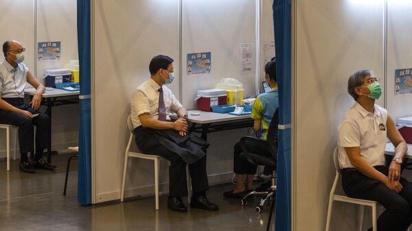 Члены правительства Гонконга делают прививку против COVID-19 вакциной CoronaVac компании Sinovac Biotech в Общественном центре вакцинации Центральной библиотеки Гонконга