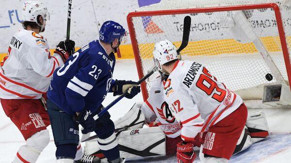 Игрок ХК Динамо Дмитрий Яшкин (второй слева) забивает шайбу в матче регулярного чемпионата Континентальной хоккейной лиги между ХК Динамо (Москва) и ХК Автомобилист (Екатеринбург).