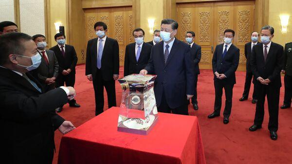 Председатель КНР Си Цзиньпин осматривает образец лунного грунта, доставленного китайским аппаратом Чанъэ-5