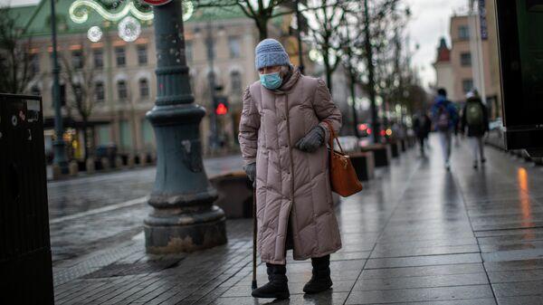 Пожилая женщина в защитной маске на улице Вильнюса