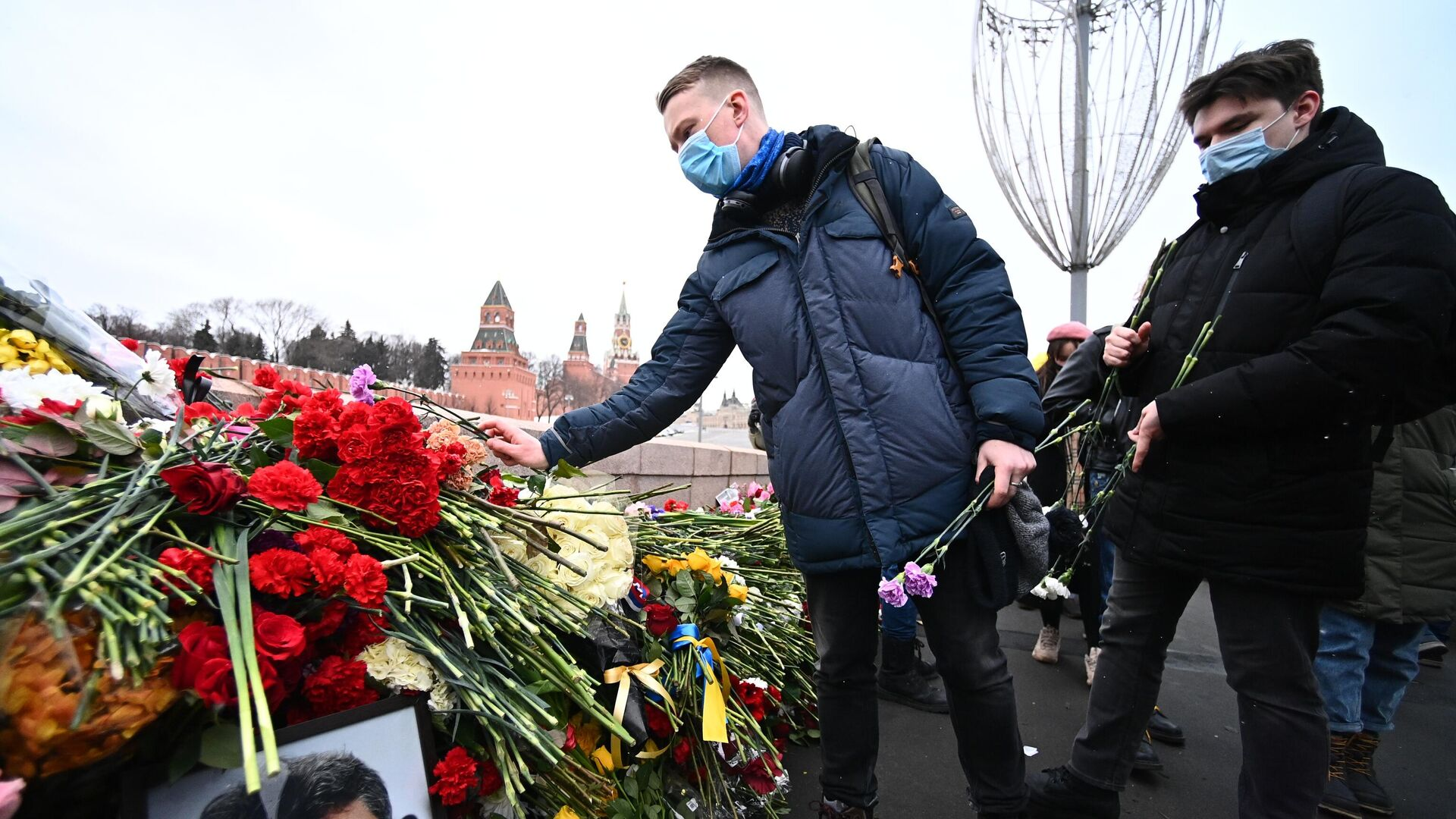Молодые люди возлагают цветы на месте гибели политика Бориса Немцова на Большом Москворецком мосту в Москве - РИА Новости, 1920, 27.02.2021