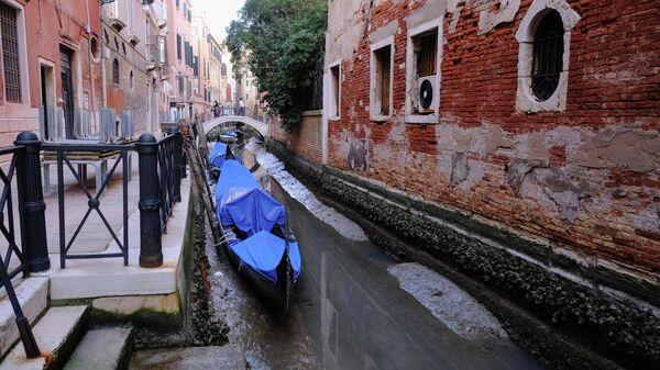 Гондолы в канале во время отлива в Венеции, Италия