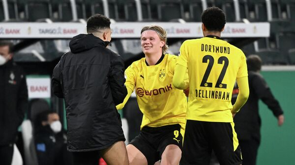 (LtoR) Dortmund's English midfielder Jadon Sancho, Dortmund's Norwegian forward Erling Braut Haaland and Dortmund's English midfielder Jude Bellingham celebrate after the German Cup (DFB Pokal) quarter-final football match between Borussia Moenchengladbach and Borussia Dortmund in Moenchengladbach, western Germany, on March 2, 2021. - Dortmund won the match 1-0 and qualified for the semi-finals. (Photo by Ina Fassbender / various sources / AFP) / DFB REGULATIONS PROHIBIT ANY USE OF PHOTOGRAPHS AS IMAGE SEQUENCES AND QUASI-VIDEO.
