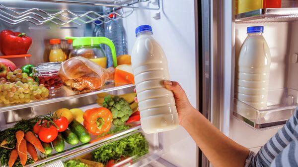 Женщина берет молоко из холодильника