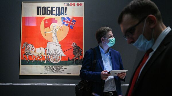 Посетители у копии плаката художника Николая Денисовского Победа! (окно ТАСС No1243 - 1244) на выставке Триумф победителей в Музее Победы в Москве