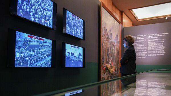 Посетительница просматривает кинодокументы на выставке Триумф победителей в Музее Победы в Москве.