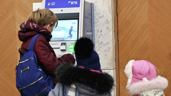 Женщина с детьми у банкомата