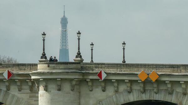 Люди в масках переходят мост Пон-Нёф в Париже, Франция