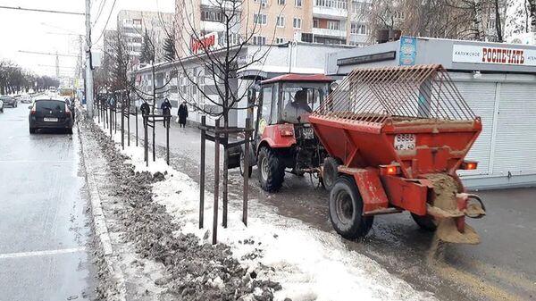 Сотрудники коммунальных служб посыпают песком тротуар в Калуге
