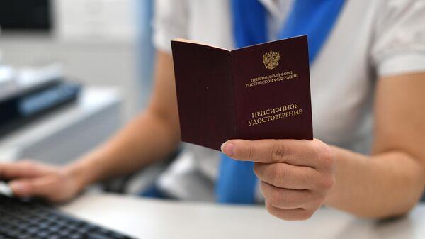 Сотрудник пенсионного фонда держит в руках пенсионное удостоверение