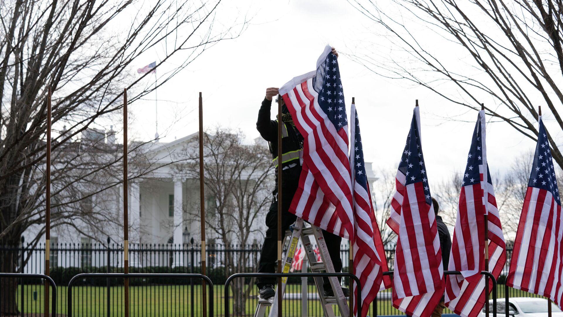 Рабочий устанавливает флаги возле Белого дома в Вашингтоне - РИА Новости, 1920, 26.03.2021