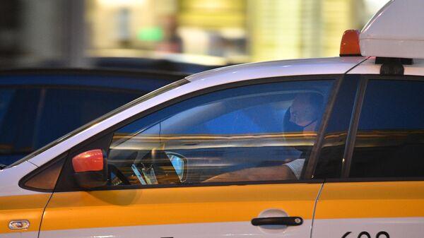 Водитель в защитной маске в автомобиле Яндекс такси на Тверской улице