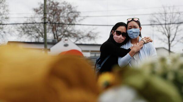 Женщины возле мемориала, организованного на месте стрельбы у Gold Spa а Атланте, США