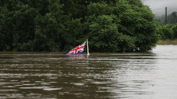 Австралийский национальный флаг на реке Хоксбери во время наводнения в пригороде Сиднея Саквилл-Норт