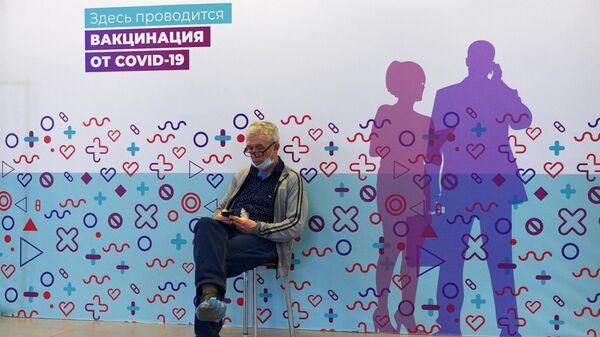 Мужчина ожидает своей очереди в мобильный пункт вакцинации от COVID-19
