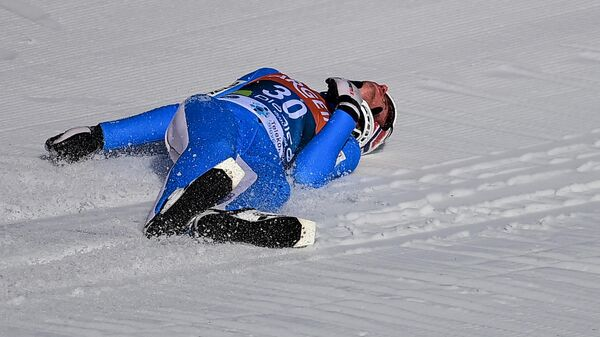 Norway's Daniel Andre Tande lies on the snow after a fall during the FIS Ski Jumping World Cup Flying Hill Individual competition in Planica on March 25, 2021. (Photo by Jure MAKOVEC / AFP)