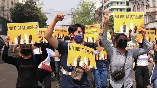 Люди с плакатами на демонстрации против военного переворота в Мьянме на улице города Янгон