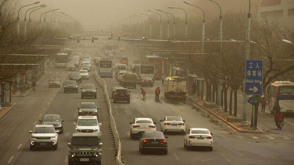 Автомобильное движение на одной из улиц Пекина после песчаной бури