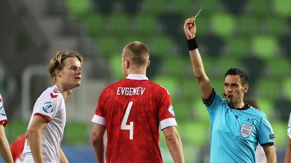 Главный судья матча Маурицио Мариани (второй справа) показывает желтую карточку игроку сборной России Роману Евгеньеву