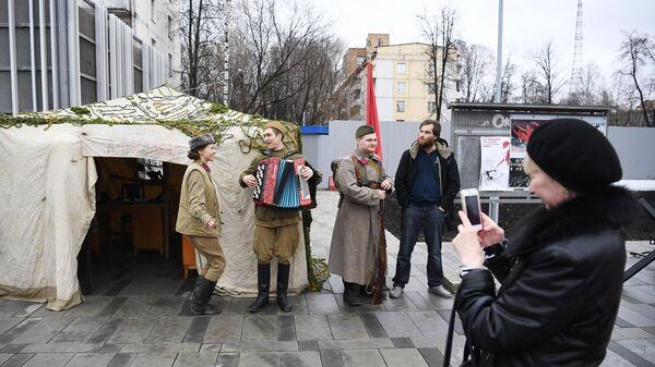 Женщина фотографирует артистов у станции Народное ополчение Большой кольцевой линии московского метрополитена.