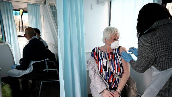 Женщина получает дозу вакцины AstraZeneca COVID-19 в Лондоне, Великобритания