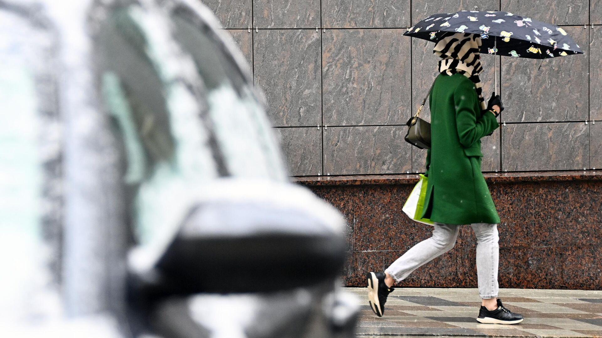 Девушка идет под зонтом во время снегопада в Москве - РИА Новости, 1920, 01.07.2021
