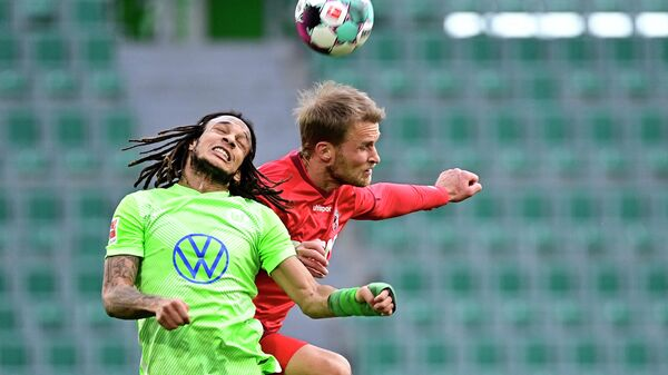 Wolfsburg's Swiss defender Kevin Mbabu (L) ansd Cologne's Swedish forward Sebastian Andersson vie for the ball during the German first division Bundesliga football match between VfL Wolfsburg and 1 FC Cologne in Wolfsburg, northern Germany, on April 3, 2021. (Photo by Tobias SCHWARZ / various sources / AFP) / DFL REGULATIONS PROHIBIT ANY USE OF PHOTOGRAPHS AS IMAGE SEQUENCES AND/OR QUASI-VIDEO