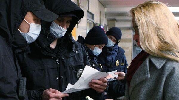 Сотрудники полиции проверяют наличие у девушки спецпропуска для проезда на общественном транспорте на одной из станций метро в Киев