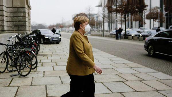 Канцлер Германии Ангела Меркель выходит из здания парламента в Берлине