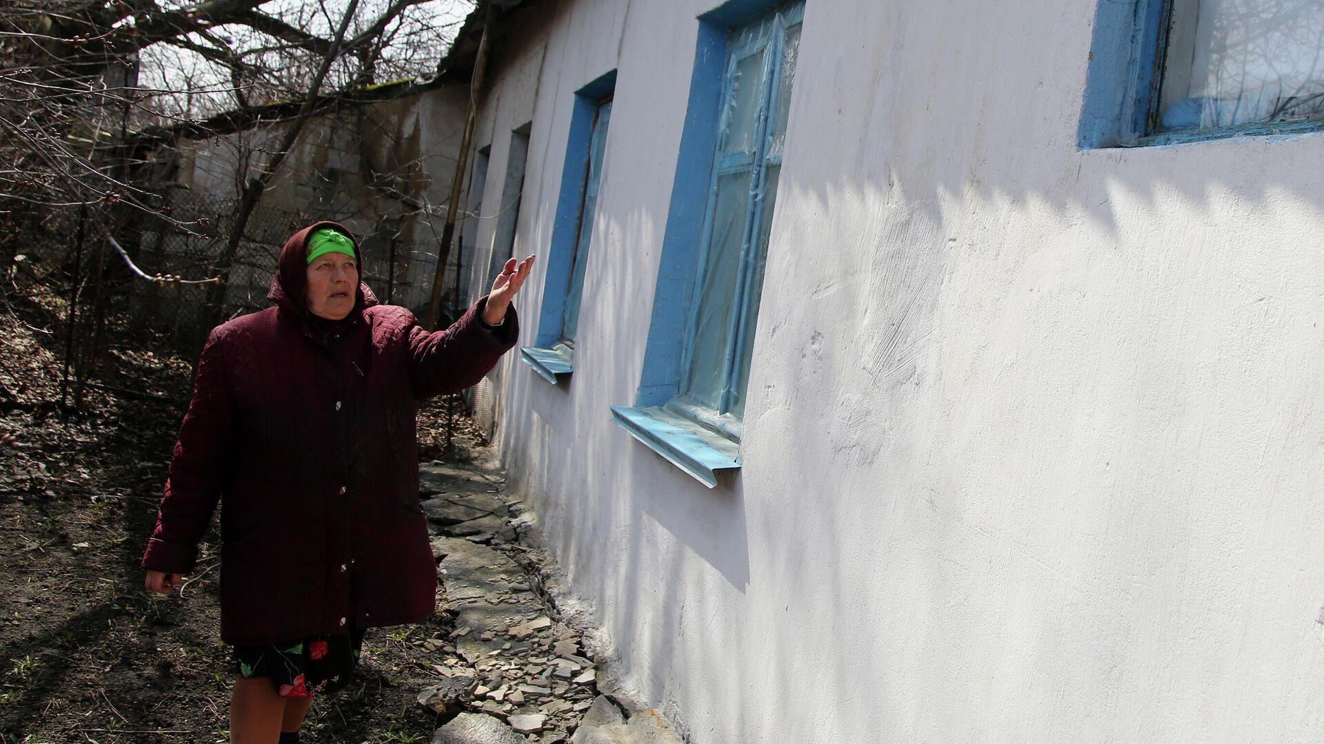 Местная жительница из села Васильевка Донецкой области показывает повреждение в своем доме, пострадавшем в результате обстрела - РИА Новости, 1920, 18.05.2021