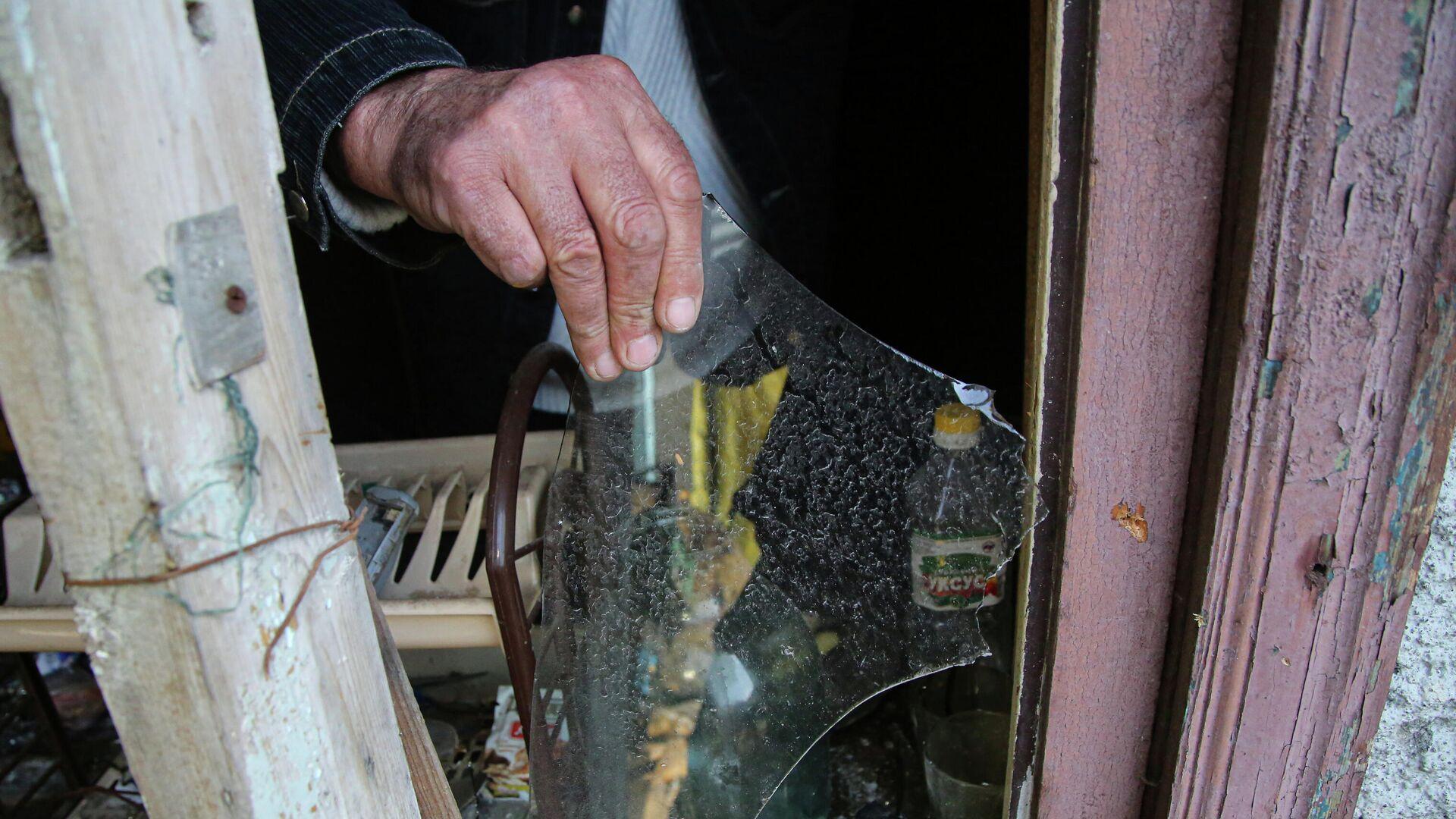 Местный житель из села Васильевка Донецкой области держит кусок разбитого стекла из разбитого окна жилого дома, пострадавшего в результате обстрела - РИА Новости, 1920, 12.04.2021