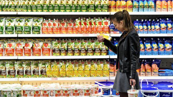 Покупательница выбирает майонез в супермаркете