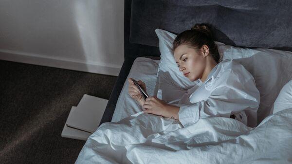 Женщина с телефоном в кровати