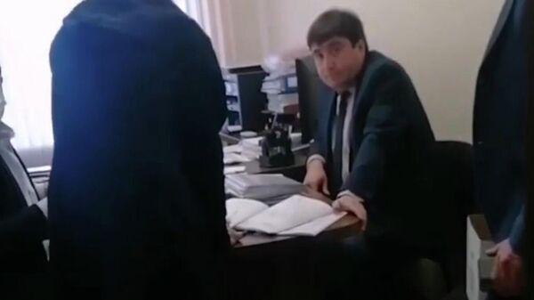 Скриншот видео, где чиновник набросился на посетителя, пришедшего на прием