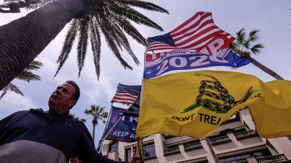 Мужчина с флагами на акции White Lives Matter в Хантингтон-Бич, Калифорния, США