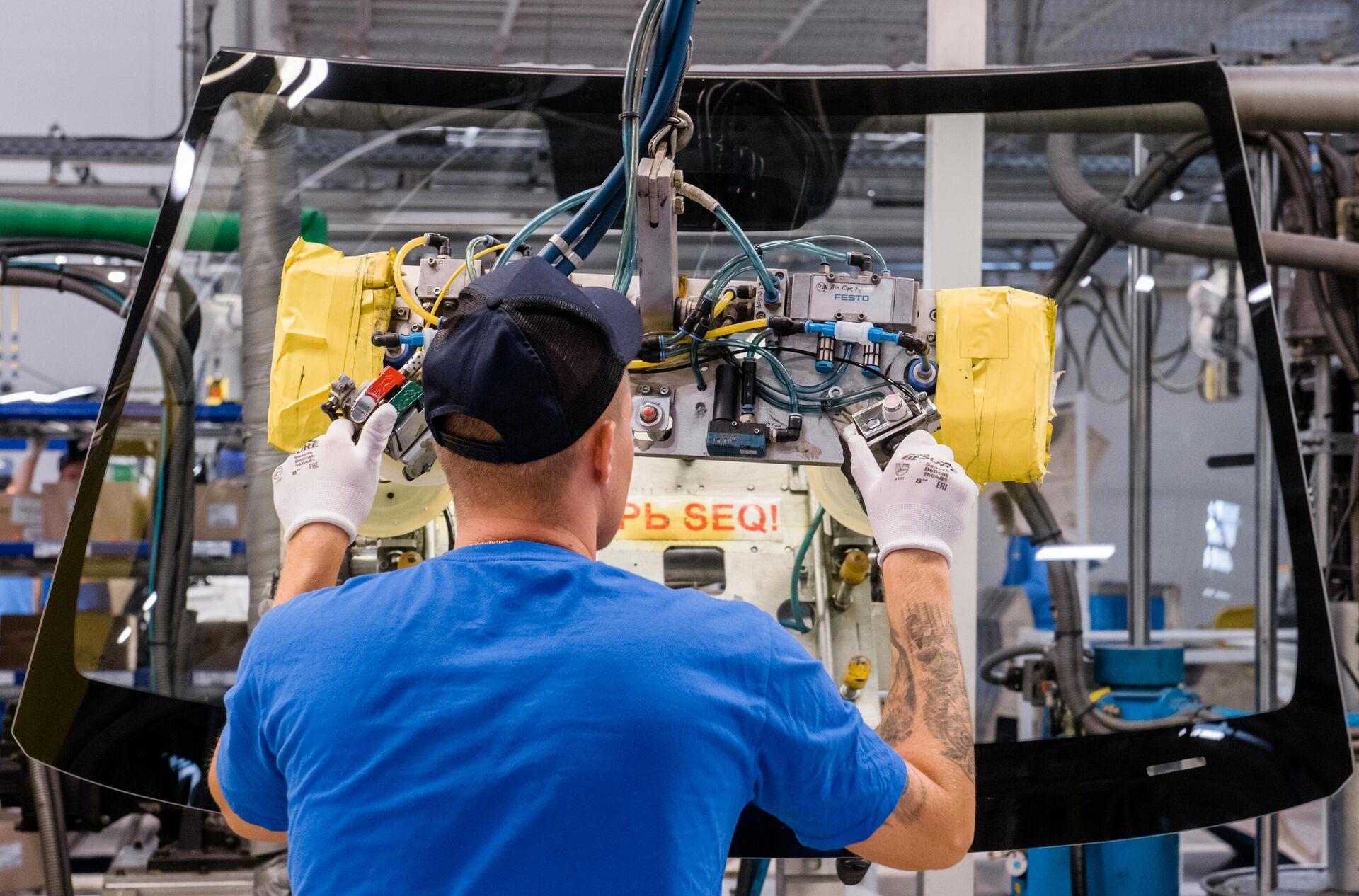 Рабочий устанавливают стекла в автомобиль на участке сборочного конвейера завода Hyundai Motor Manufacturing Rus в Санкт-Петербурге - РИА Новости, 1920, 12.04.2021