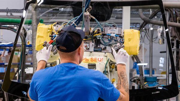 Рабочий устанавливают стекла в автомобиль на участке сборочного конвейера завода Hyundai Motor Manufacturing Rus в Санкт-Петербурге