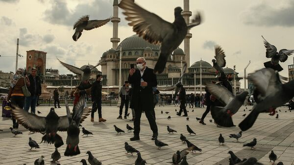 Мужчина кормит голубей на площади Таксим в Стамбуле