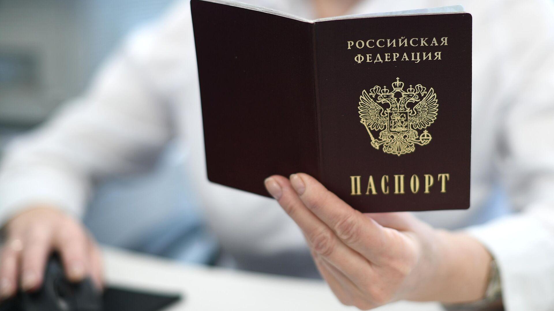 Сотрудник ПФР держит в руках российский паспорт - РИА Новости, 1920, 11.06.2021