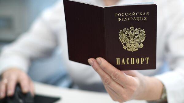 Сотрудник ПФР держит в руках российский паспорт